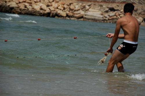 While a strong young man pulls a net taught along the Mediterranean in order to catch what the sea dreams.