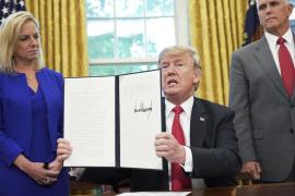 Watched by Homeland Security Secretary Kirstjen Nielsen and Vice President Mike Pence, U.S. President Donald Trump shows an executive order on immigration that he signed in the Oval Office of the White House on Wednesday in Washington. Mandel Ngan/AFP/Getty Images